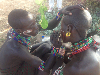 Men of the Hamer tribe applying decorative paint.