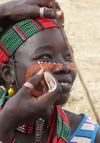 A Hamer woman has her face decorated.